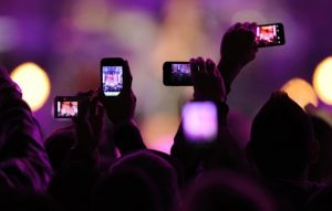 Fans take photos with their mobile phones during the VH1 Divas Salute The Troops show in San Diego