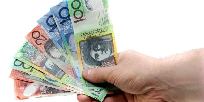 a hand holding a wad of australian banknotes